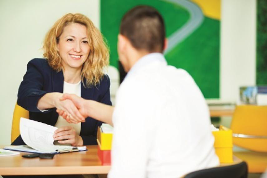 Banker shaking hands across desk with customer