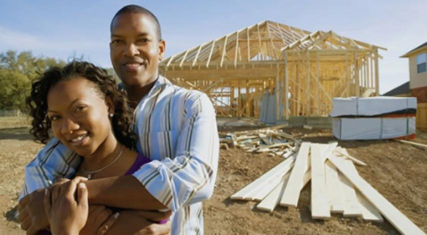 couple embracing in front of house being built