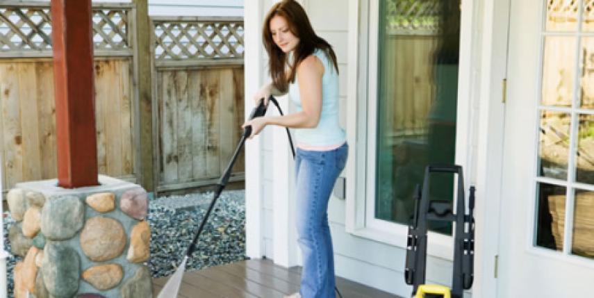 woman powerwashing patio