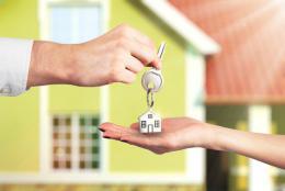 handing over keys in front of house