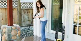 woman powerwashing patio